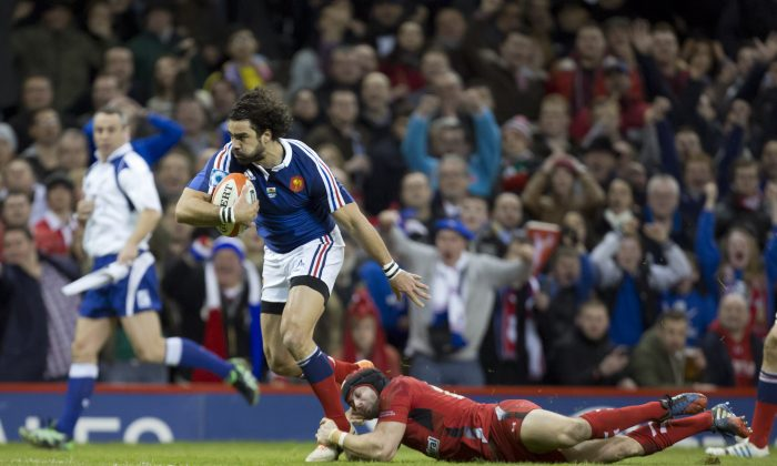 France's Jean-Marc Doussain evades a tackle from Wales' Leigh Halfpenny as he heads over to score only to have his try declared void during their Six Nations rugby union international match at the Millennium Stadium, Cardiff, Wales, Friday, Feb. 21, 2014. (AP Photo/Jon Super)