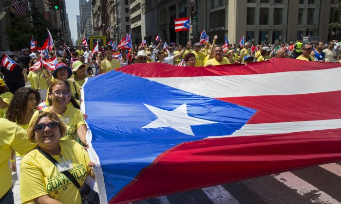 People carry a large Puerto Rican flag marching in the National Puerto Rican Day Parade in New York on June 9, 2013. (Craig Ruttle/AP)