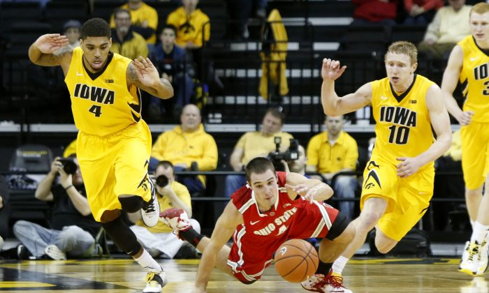 Ohio State Buckeyes guard Aaron Craft (4) drives for the ball surrounded by Iowa's Roy Devyn Marble (4) and Mike Gesell (10) during the second half of a NCAA basketball game at Carver-Hawkeye Arena in Iowa City, Iowa on Tuesday, Feb 4, 2014. (AP photo/Cliff Jette)