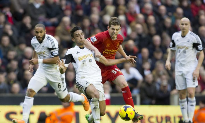 Liverpool's Jon Flanagan, centre, fights for the ball against Swansea City's Neil Taylor during their English Premier League soccer match at Anfield Stadium, Liverpool, England, Sunday Feb. 23, 2014. (AP Photo/Jon Super)