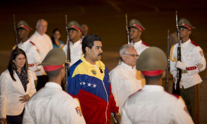 Venezuela's President Nicolas Maduro, center, arrives at the Jose Marti International airport in Havana, Cuba, Sunday, Jan. 26, 2014. (AP Photo/Ramon Espinosa)