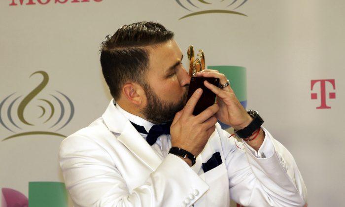 Poncho Lizarraga of Banda El Recodo kisses the trophy while posing for photos at the Premio Lo Nuestro Latin Music Awards show in Miami, Thursday, Feb. 20, 2014. (AP Photo/Alan Diaz)