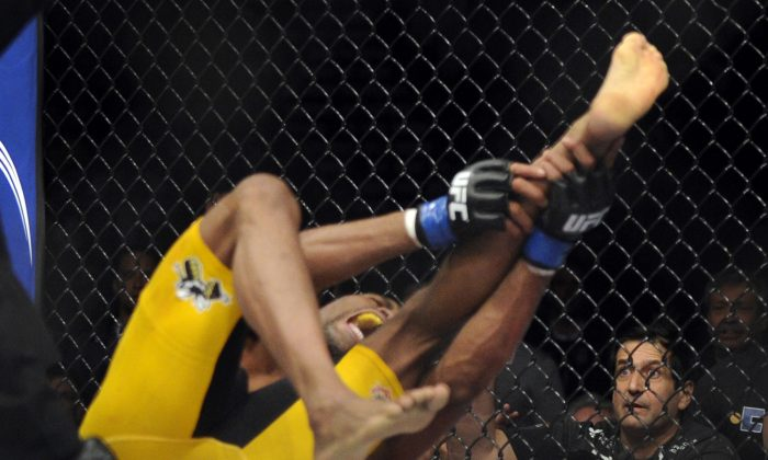 Anderson Silva screams after injuring his leg in a December 28, 2013 fight. Jon Jones has joined others in saying that Silva should retire. (AP Photo/David Becker)