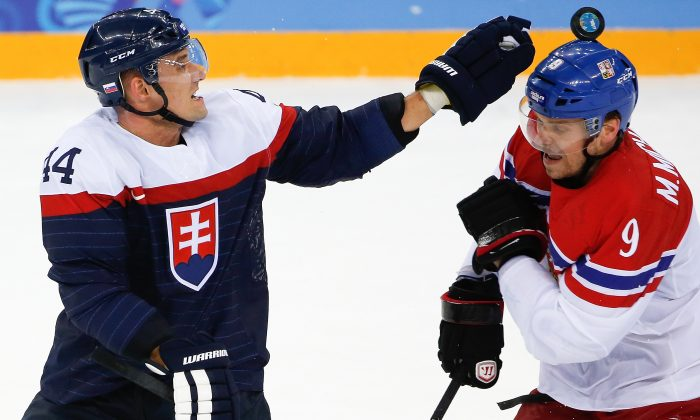 Slovakia defenseman Andrej Sekera reaches for the puck as it bounces off of Czech Republic forward Milan Michalek, helmet during the third period of the 2014 Winter Olympics men's ice hockey game at Shayba Arena, Tuesday, Feb. 18, 2014, in Sochi, Russia. the Czech Republic defeated Slovakia 5-3. (AP Photo/Petr David Josek)