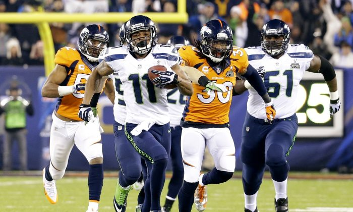 Seattle Seahawks' Percy Harvin (11) runs from Denver Broncos' David Bruton (30) while returning a kickoff 87-yards for a touchdown during the second half of the NFL Super Bowl XLVIII football game Sunday, Feb. 2, 2014, in East Rutherford, N.J.  (AP Photo/Ted S. Warren)