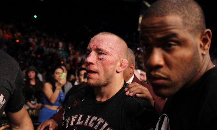 Georges St. Pierre, of Canada, exits the octagon following a UFC 167 mixed martial arts championship welterweight bout against Johny Hendricks on Saturday, Nov. 16, 2013, in Las Vegas. St. Pierre won by split decision. (AP Photo/Isaac Brekken)