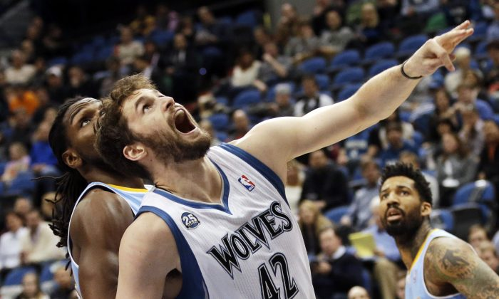 Minnesota Timberwolves' Kevin Love, right, reacts as he and Denver Nuggets's Kenneth Faried watch Love's shot drop in the first quarter of an NBA basketball game Wednesday, Feb. 12, 2014, in Minneapolis. (AP Photo/Jim Mone)