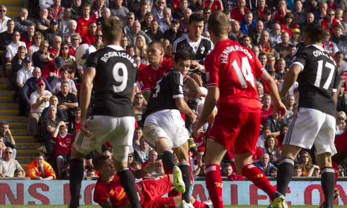 Southampton's Dejan Lovren, centre, scores against Liverpool during their English Premier League soccer match at Anfield Stadium, Liverpool, England, Saturday Sept. 21, 2013. (AP Photo/Jon Super)