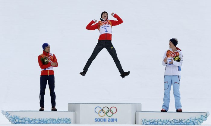 Germany's Eric Frenzel celebrates winning the gold as he is flanked by Japan's silver medal winner Akito Watabe, left, and Norway's bronze medal winner Magnus Krog  during the flower ceremony after the cross-country portion of the nordic combined at the 2014 Winter Olympics, Wednesday, Feb. 12, 2014, in Krasnaya Polyana, Russia. (AP Photo/Matthias Schrader)