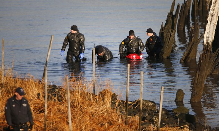 After an arm, torso, and legs were discovered, a New York Police Department dive unit continues the search for human remains along a rocky shoreline in the Queens borough of New York, Jan. 29, 2014. (Jason DeCrow/AP)