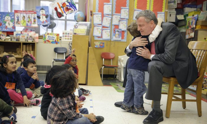 New York Mayor Bill de Blasio hugs a child after reading a book to a prekindergarten class at P.S. 130 in New York, Feb. 25, 2014. (AP Photo/Seth Wenig)