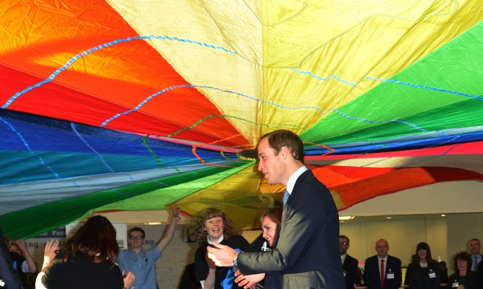 Britain's Prince William, Duke of Cambridge, joins in with the Parachute Game at the Diana Award Inspire Day at Haven Point Leisure Centre in South Shields, north-east England on Nov. 22, 2013. The Duke of Cambridge met with young people taking part in workshops on anti-bullying and project management skills at Haven Point Leisure Centre.  (Neil Jones/AFP/Getty Images)