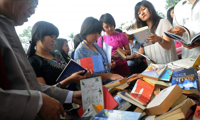Visitors browse books on sale at a stand outside a hotel hosting Burma's first international literary festival, in Yangon on Feb. 1, 2013. Speakers at the Irrawaddy Literary festival included luminaries from the book world, talented local authors, and event patron Aung San Suu Kyi. (Soe Than Win/AFP/Getty Images)