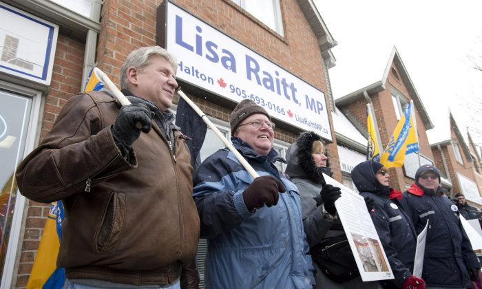 Postal workers demonstrate in front of Transport Minister Lisa Raitt's Milton, Ont., Wednesday, Dec. 18, 2013. CUPW delivered thousands of postcards to Raitt from Canadians who are angry that Canada Post is closing and downsizing public post offices. (The Canadian Press/Frank Gunn)