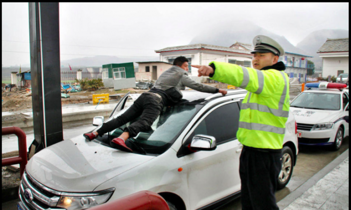 Screenshot showing a man holding onto the front of a SUV stuck at a toll booth, following a dispute over money. (Screenshot/ifeng.com)