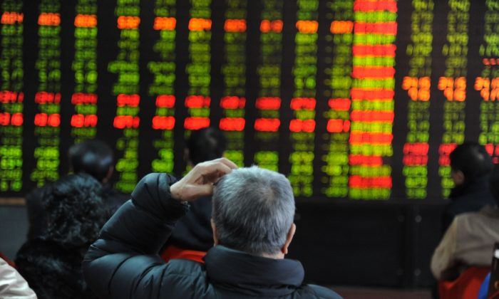 An investor scratches his head while watching the electronic board at a stock exchange hall in Shenyang, China on Feb. 19, 2013. Financial analysts are concerned about China's growing credit bubble. (ChinaFotoPress/Getty Images)