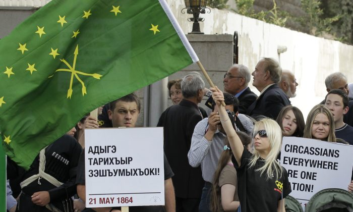 Members of Jordan's Muslim Circassian minority hold banners and wave Circassian flags during a demonstration outside the Russian Embassy in Amman on May 21, 2012, to mark the 148th year since imperial Russian troops drove them out of their North Caucasus homes. (Khalil Mazraawi/AFP/GettyImages)
