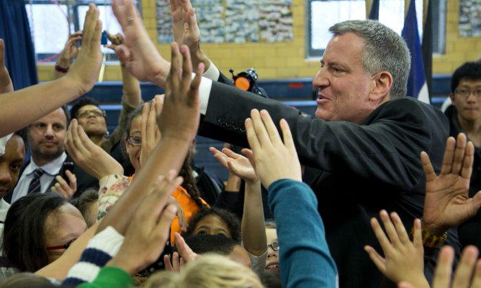 New York City Mayor Bill de Blasio exchanges high-fives with school children at M.S. 51 in Brooklyn, New York, Dec. 30, 2013. (Mark Lennihan/AP)