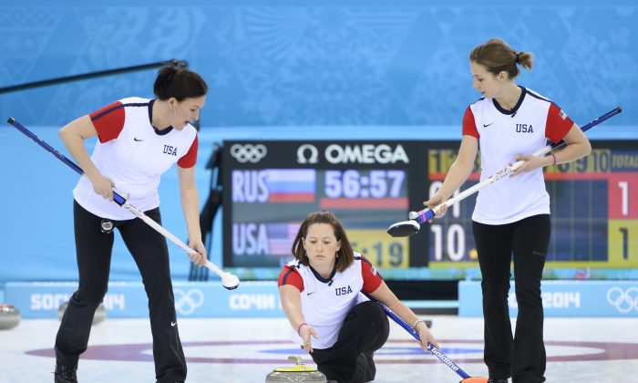 U.S. vice-skip Debbie McCormick (C) throws the stone during the women's curling round robin session 2 match between Russia and USA at the Ice Cube curling centre in Sochi on February 11, 2014 during the 2014 Sochi winter Olympics. (Jonathan Nackstrand/AFP/Getty Images)