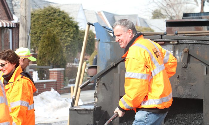 Mayor Bill de Blasio shovels asphalt to fill a pothole in Queens, New York, on Feb. 20, 2014. (Allex Xie)