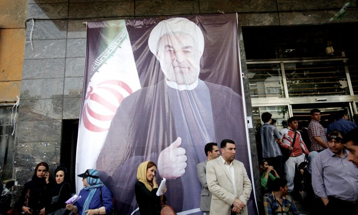 Iranians gather under a giant portrait of Hassan Rouhani during his campaign for president in downtown Tehran on June 15, 2013. (Behrouz Mehri/AFP/Getty Images)