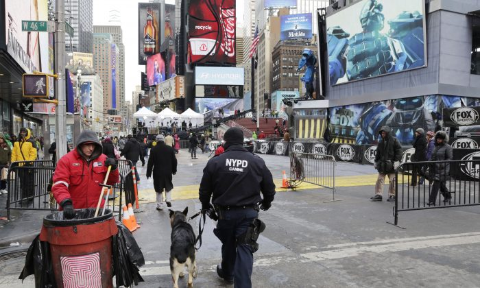 An NYPD officer patrols with a dog in Times Square, New York, Jan. 26, 2014. Recent incidents involving the emotionally disturbed include a accidental shooting of bystanders near Times Square in September 2013. (Mark Lennihan/AP)