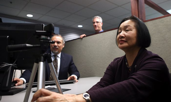 Oakland mayor Jean Quan takes her photo as she registers for the new Oakland Municipal identification card  in Oakland, Calif., on Feb. 1, 2013. Oakland became the first city in the nation to offer a municipal identification card. New York City Mayor Bill de Blasio vowed to make municipal ID cards available to city residents by the end of 2014. (Justin Sullivan/Getty Images)