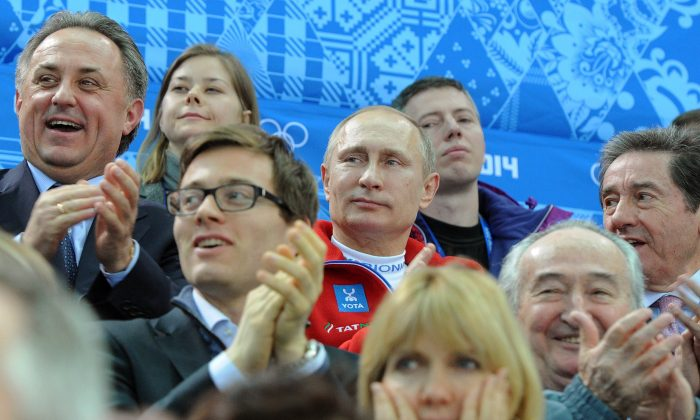 Russia's President Vladimir Putin (C) watches the figure skating team free program during the Sochi Winter Olympics, Feb. 9, 2014. (Mikhail Klimentyev/AFP/Getty Images)
