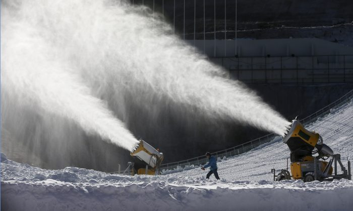 Snow machines blow snow into the air at the ski jumping venue at the Winter Olympics, Feb. 3, 2014 (AP Photo/Dmitry Lovetsky)