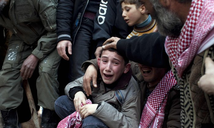 Ahmed (C) mourns his father, Abdulaziz Abu Ahmed Khrer, who was killed by a Syrian Army sniper, during his funeral in Idlib, northern Syria, March 8, 2012. A new UN report on the situation of children in Syria reveals that at least 10,000 children have been killed in Syria's civil war so far, and an estimated 5 million have been affected. (AP Photo/Rodrigo Abd)