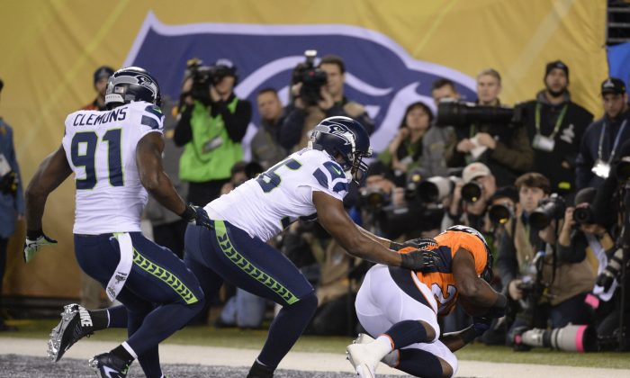 Chris Clemons (L) and Cliff Avril (C) of the Seattle Seahawks put pressure on Knowshon Moreno of the Denver Broncos for a safety on the first play of Super Bowl 48 at MetLife stadium in East Rutherford, New Jersey, on February 2, 2014. (Timothy A. Clary/AFP/Getty Images)