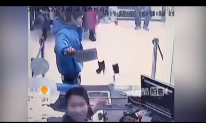 Screenshot of security footage showing a man with a cleaver trying to rob a bank in Shanghai, while talking on his cellphone. (Screenshot/YouTube)
