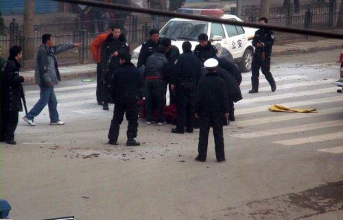 """Chinese authorities have threatened to """"strike hard"""" at families and communities of would-be self-immolators in Ngaba Prefecture of Sichuan Province, when the majority of self immolations by Tibetans have occured. This photo shows police surrounding the body of a monk who self-immolated in Ngaba in March 2009. (Internet photo)"""