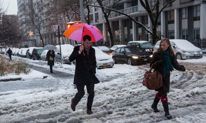 People attempt to walk across a snowy street in Greenwich Village, New York, Feb. 5. 2014. New York and surrounding regions are facing a set of snowstorms Thursday, bringing snow, ice, sleet, and freezing rain. (Andrew Burton/Getty Images)