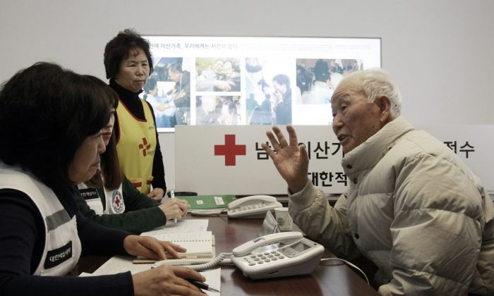 South Korean Lee Kyun-myoung, 93, right, talks with Red Cross members as he fills out application forms to reunite with his family members living in North Korea, at the Korea Red Cross headquarters in Seoul, South Korea, Thursday, Feb. 6, 2014. (AP Photo/Ahn Young-joon)