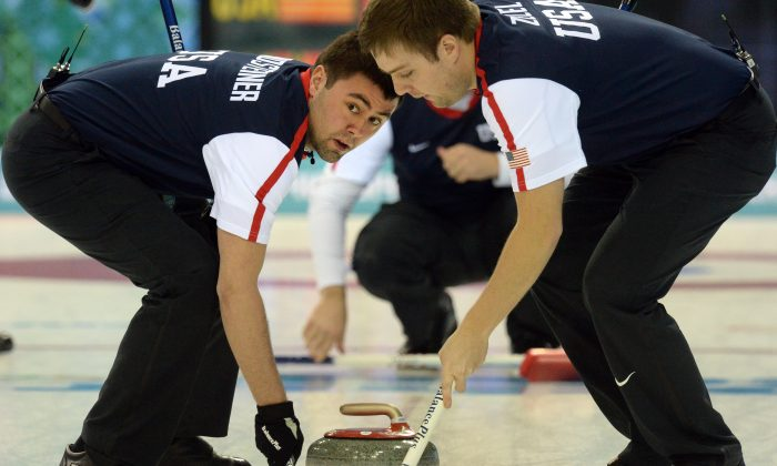 Jared Zezel (R) and John Landsteiner of the US clean the way for the stone during the men's curling round robin session 2 match between Norway and USA at the Ice Cube curling centre in Sochi on February 10, 2014 during the 2014 Sochi Winter Olympics. (Yuri Kadobnov/AFP/Getty Images)
