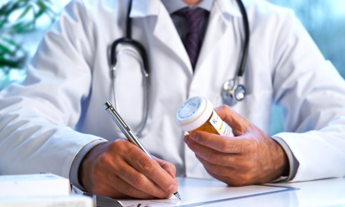 A doctor fills out a prescription in this file photo. (Shutterstock*)