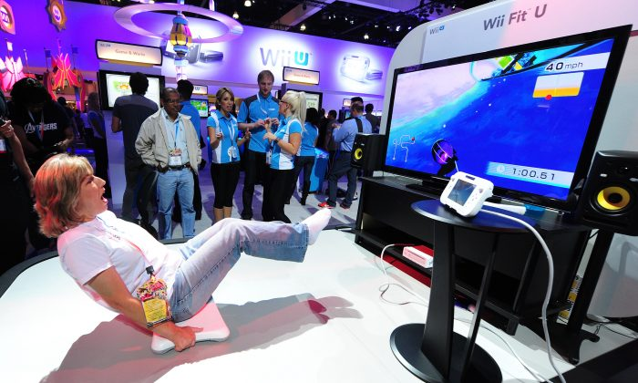 A woman works her abs while playing the 'Core Luge' game from Wii Fit U from the new Wii U console on the third day of the E3 videogame extravaganza in Los Angeles on June7, 2012 in California. (Frederic J. Brown/AFP/GettyImages)