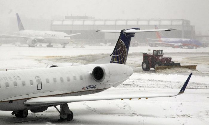 A snowplow moves snow off taxiways at Newark Liberty International Airport, Monday, Feb. 3, 2014, in Newark, N.J. (AP Photo/Mike Stewart)