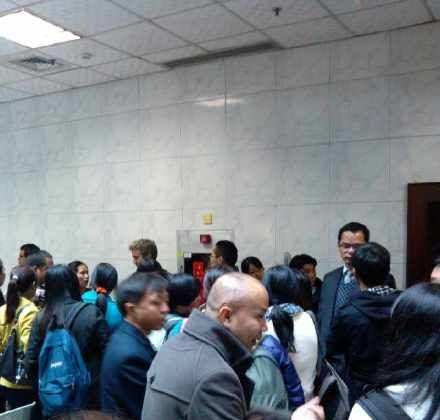 Witnesses and supporters of labor activist Wu Guijun wait outside the courtroom for his trial to open in Shenzhen, Guangzhou Province on Feb. 17, 2013. Wu's lawyer Pan Jun stands in the background behind the crowd in a suit and vest, with glasses. (Weibo.com)