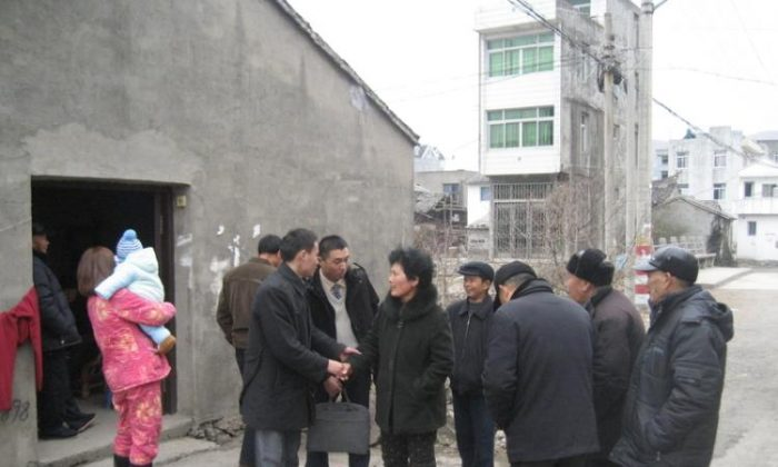 In this photo, Wei Shuishan and Xue Mingkai (center, wearing white sweater), two key members of China Democracy Party, visit Zhaiqiao Village to interview the family of a village head who died a suspicious death, Qian Yunhui, Jan. 25, 2010. On Jan. 29, 2013 Xue Mingkai's father died a mysterious death, which activists wish to investigate. (Courtesy of an informer)