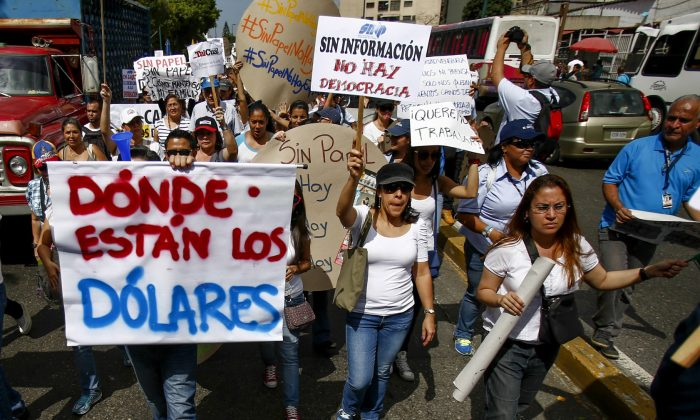 """Workers from the newspaper El Impulso shout slogans to demand the government free up U.S. dollars for the company to be able to buy and import newsprint in Caracas, Venezuela, Tuesday, Feb. 11, 2014. The sign at left reads in Spanish """"Where are the dollars."""" As newspapers have been beset for years by currency controls that make it difficult to import supplies, the situation has turned critical as reserves of newsprint have fallen to an all-time low, according to Venezuelan Press Block, which represents the nation's broadsheets. (AP Photo/Alejandro Cegarra)"""