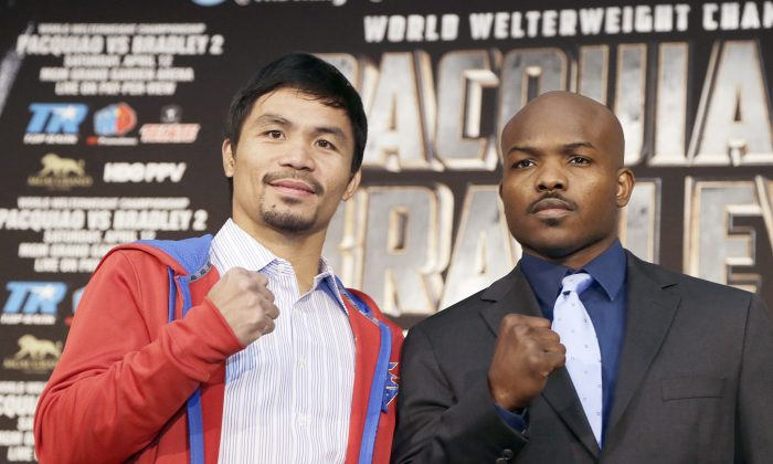 Manny Pacquiao, left of the Philippines, and Tim Bradley pose at a news conference to promote their upcoming WBO welterweight championship boxing rematch in Beverly Hills, Calif., Tuesday, Feb. 4, 2014.  Pacquiao and Bradley's first match on June 9, 2012 was a split decision in favor of Bradley, which ended Pacquiao's welterweight title reign as well as his seven-year, 15-bout winning streak. (AP Photo/Reed Saxon)