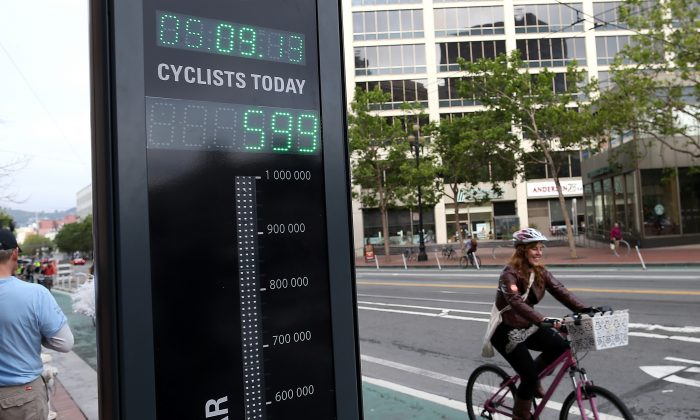 A bicyclist rides by an automated real-time bike counter on Market Street in San Francisco, Calif., on May 9, 2013. The combined efforts of two organizations are on track to introduce a bike counter in New York City. (Justin Sullivan/Getty Images)