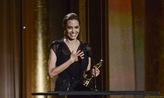 """FILE - In this Nov. 16, 2013 file photo, actress and honoree Angelina Jolie receives the Jean Hersholt Humanitarian Award at the 2013 Governors Awards in Los Angeles.  The 38-year-old Oscar winner came to the Dolby Theater in Los Angeles on Thursday, Feb. 27, 2014, to run through the lines she'll say in front of millions at the 86th Academy Awards on Sunday, March 2, 2014. Afterward, she hung around chatting to show producers and introduced herself as """"Angie"""" to a group of college students serving as trophy carriers this year. (Photo by Dan Steinberg/Invision/AP, file)"""