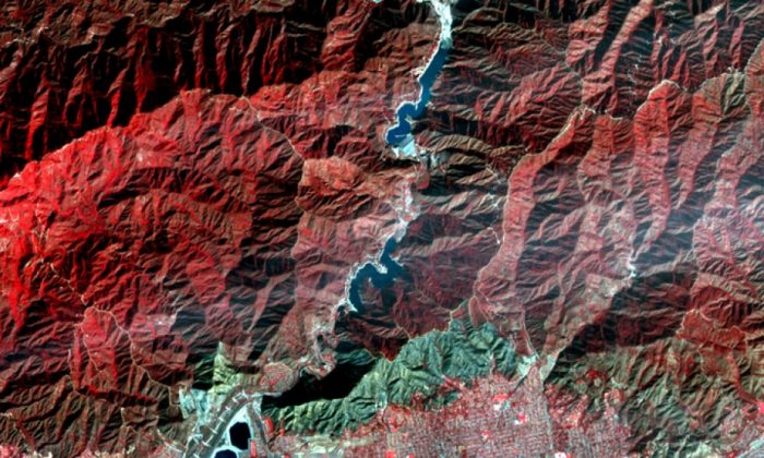 A satellite image from NASA shows the area above Glendora and Azusa that is now known as the Colby burn scar. The blue-gray area at the base of the mountains is the scar, while red indicates vegetation.