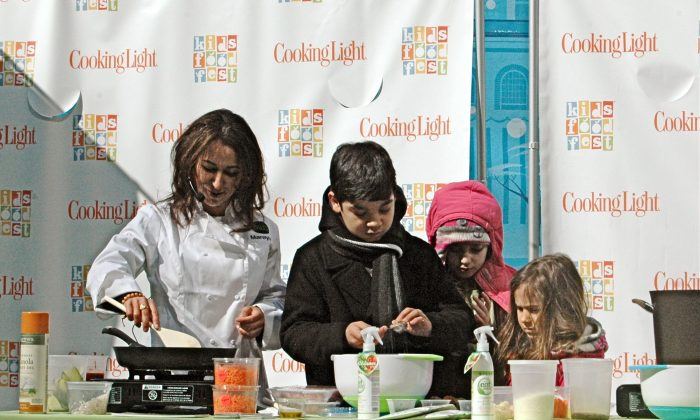 """Mareya Ibrahim, known as the """"Fit Foodie,"""" cooks up a healthier spaghetti and meatballs with her young helpers in Bryant Park on March 2013. She brought a creative, unexpected twist to the classic kids' dish. (Channaly Philipp/Epoch Times)"""