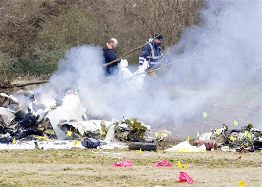 A body is removed from a plane crash that killed everyone on board outside the Bellevue YMCA in Nashville, Tenn., Tuesday, Feb. 4, 2014. Authorities believe four members of the same family were on board the flight from Great Bend, Kan. (AP Photo/The Tennessean, Samuel M. Simpkins)