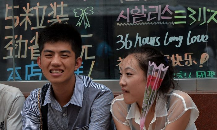A young girl holds a rose next to her boyfriend in Beijing on August 13, 2013. (MARK RALSTON/AFP/Getty Images)
