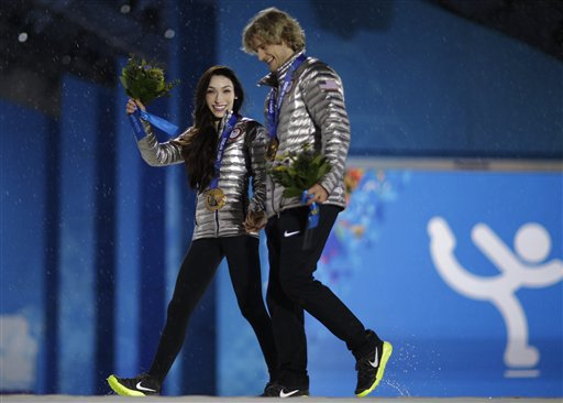 Ice dance figure skating gold medalists Meryl Davis and Charlie White of the United States exit the stage following their medals ceremony at the 2014 Winter Olympics, Tuesday, Feb. 18, 2014, in Sochi, Russia. (AP Photo/David Goldman)
